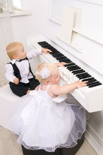boy and girl playing on a white piano