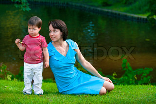 Cute two years old boy with his young mom in park