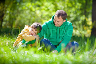 Cute little boy hugs his father outdoors