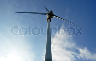 Wind turbine as alternative energy source against blue cloudy sky