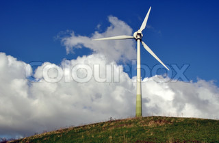 Wind turbine as alternative energy source on green hill against blue cloudy sky with bushes and fencesin front