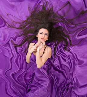 beautiful girl with long dark hair a background of purple silk