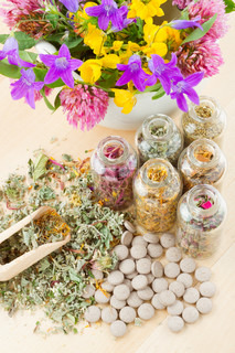 different healing herbs in glass bottles, flowers bouquet in mortar, tablets, herbal medicine