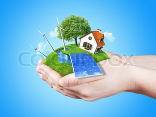 Hands holding clear green meadow with sun battery block, wind mill turbines and countryside house. Concept for ecology, alternative energy, freshness, freedom. Green fields collection.