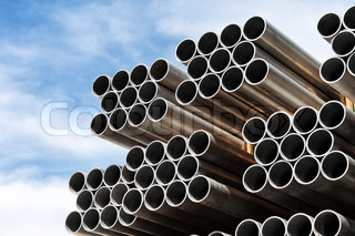Pile of new steel pipes on a construction site