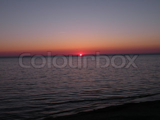 almost vanished sun at horizon over the sea in denmark