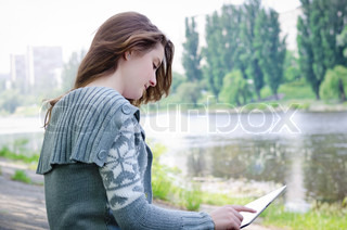 Girl sitting outdoors using a touchscreen tablet along a riverbank
