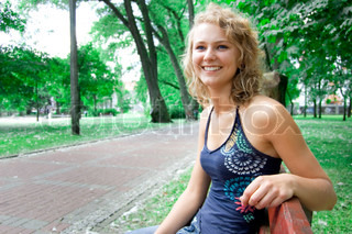 Young beautiful girl sitting on a park bench and smiles