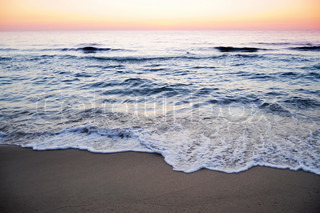 Waves splashing at the shore at sunrise