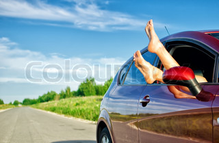 Woman's legs out of the car window Concept of carefree funny trip