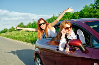 Two pretty happy girls in the car Concept of carefree roadtrip