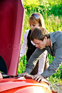 Man a nd woman are looking at the car engine