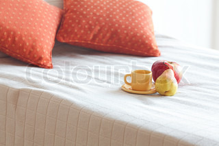 cup of tea,apple and pear on the bed