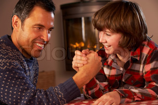Father And Son Arm Wrestling By Cosy Log Fire