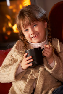 Young Girl Relaxing With Hot Drink By Cosy Log Fire