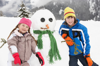 Two Young Children Building Snowman On Ski Holiday In Mountains