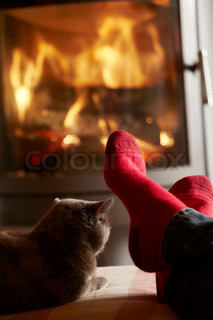 Close Up Of Mans Feet Relaxing By Cosy Log Fire With Cat