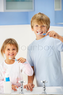 Boy and girl cleaning teeth in bathroom