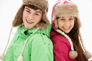 Portrait Of Teenage Couple In Snow Wearing Fur Hats