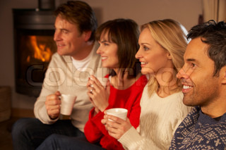 Group Of Middle Aged Couples Sitting On Sofa With Hot Drinks Watching TV