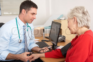 British doctor taking senior woman's blood pressure