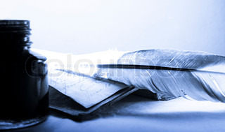 Old book with feather and inkpot in blue
