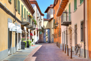 Narrow stone paved street among colorful houses in town of Alba in Piedmont, Northern Italy.