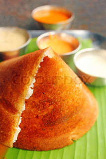 Masala Dosa - Closeup macro photo one of the most popular south indian breakfast served with different types of chutney, sambar and ghee Isolated on white and with clipping mask