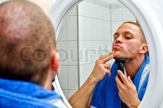 Male with towel shaving in bathroom in front of the mirror