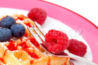 belgian waffles with syrup orserved on a plate, garnished with raspberries and blueberry