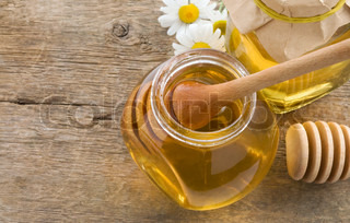 glass jar of honey and stick on wood