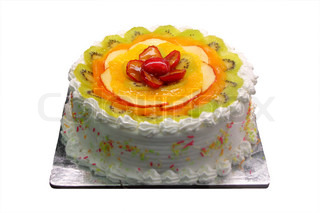 Delicious and yummy white birthday and party cake with sliced fruit pieces of kiwi, orange, plums and apple decorated on the pastry surface isolated on white background with clipping path