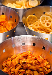 Steel containers with delicious deep fried potato and banana crisps or chips in golden brown colors which are served as side dishes along with main course of meals and as fast food