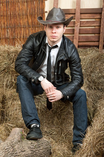 Handsome cowboy in leather jacket in the rural interior