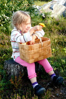 smiling little mushroom collecting girl sitting in the forest showing a yellow chanterelle