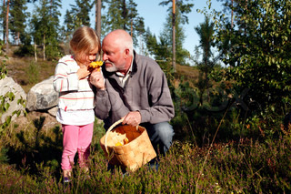little girl and her grandpa sniffing at a chanterelle
