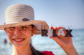 Teen girl at a beach holding word 'Relax'