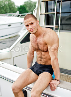 Muscular handsome sailor on his yacht