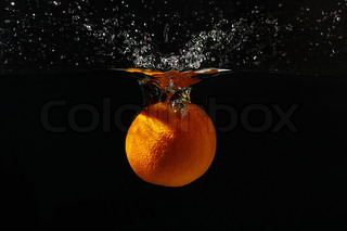 Orange falling into the water with a splash on a black background