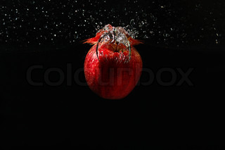 Apple falling into the water with a splash on a black background