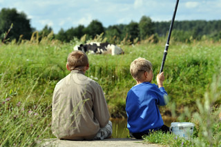 Two small boys fishing with a cow