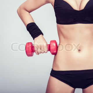 athletic body with dumbbells close-up