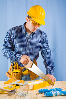 carpenter works with handsaw