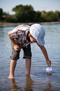 Boy launchesa small sailboat in the river