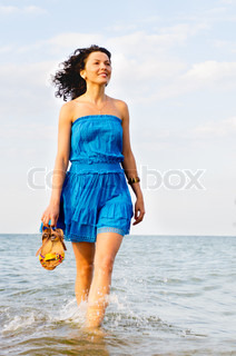 Woman running along the edge of the surf in hand beach slippers