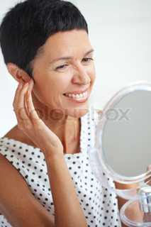 Portrait of beautiful middle aged woman holding cosmetic mirror