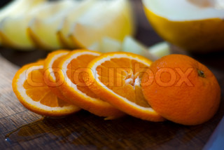 Closeup of a row slices of a juicy orange in a relaxed stack on a chopping board with soft focusedrow of slices of yellow honey dew melon in the background