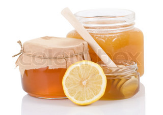 pot full of honey and lemon isolated on white