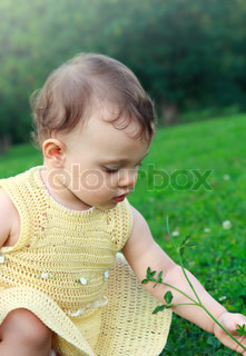 Adorable baby girl in dress looking on flower and green grass on summer nature