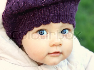 Funny baby in hat with big blue eyes looking o nature green background